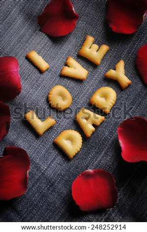 Cookies ABC in the form of word I LOVE DADY alphabet with red rose petal on old jean background, Valentines day - stock photo