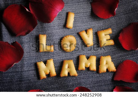Cookies ABC in the form of word I LOVE MAMA alphabet with red rose petal on old jean background, Valentines day - stock photo