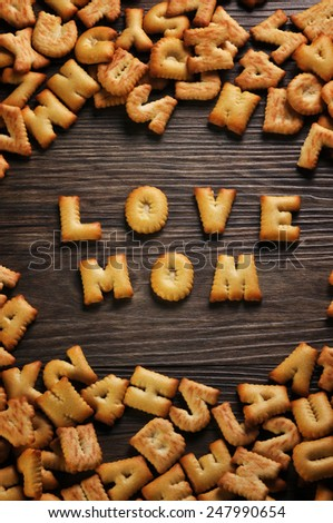 Cookies ABC in the form of word LOVE MOM alphabet on old wood background, Valentines day - stock photo