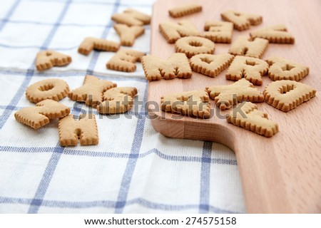 Cookies ABC on wooden plate - stock photo