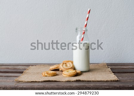 Cookies and bottle of milk on wood table - stock photo