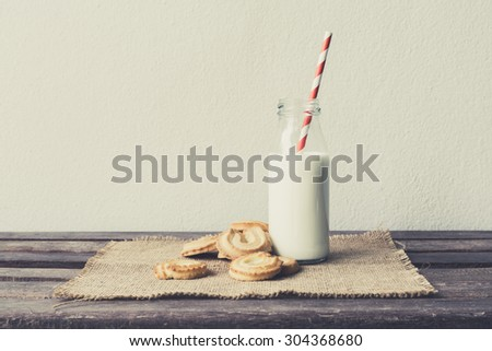 Cookies and bottle of milk on wood table with vintage style - stock photo
