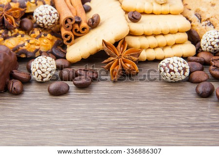 Cookies and candies with coffee beans and spices on wooden
