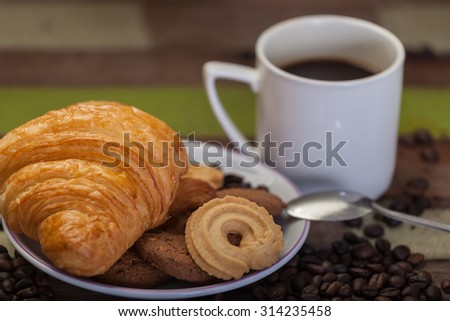Cookies and croissant with a cup of coffee background - stock photo