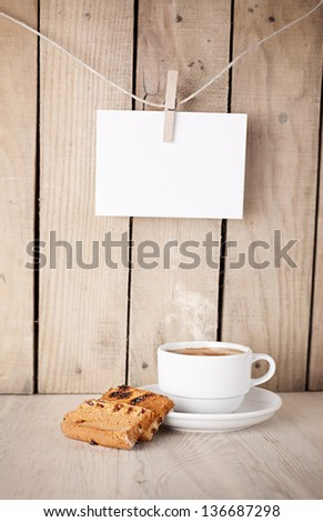 cookies and cup of coffee in front of a wooden wall with blank note paper hanged - stock photo