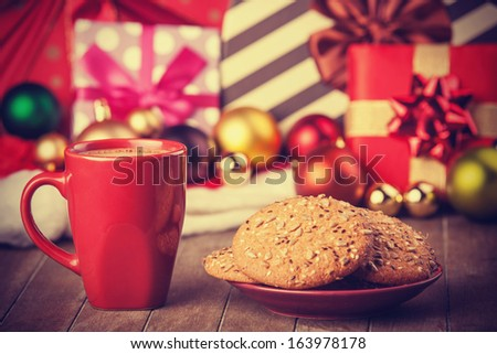 Cookies and cup of coffee with christmas gifts at background - stock photo