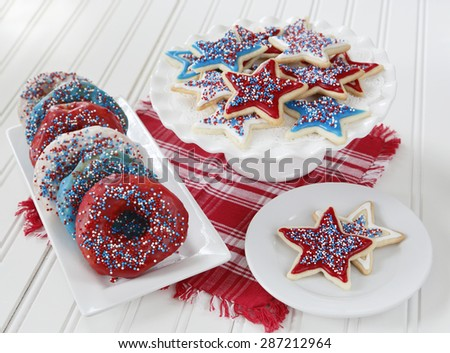 Cookies and donuts decorated with icing and sprinkles in red, blue, and white to celebrate 4th of July in America. - stock photo
