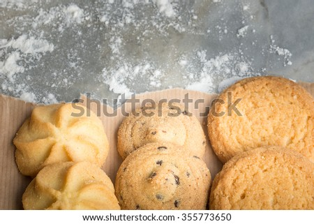 Cookies and flour. Shortbread biscuits. In a rustic kitchen on an old marble textured surface. Remnants of flour. Variety. - stock photo