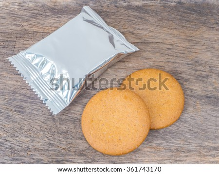 cookies and foil package on wood background - stock photo