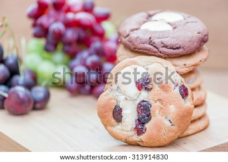Cookies and fruit on wood board