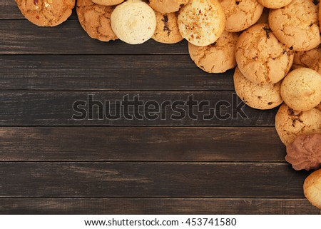 Cookies and sweet biscuits at brown wood, background with copy space. Oatmeal and chocolate drops cookies border, dessert for tea. - stock photo