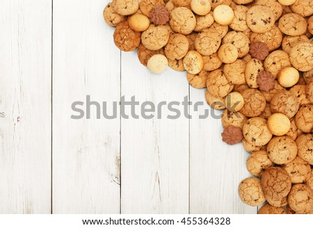 Cookies and sweet biscuits at white wood, background with copy space. Oatmeal and chocolate drops cookies border, dessert for tea. - stock photo