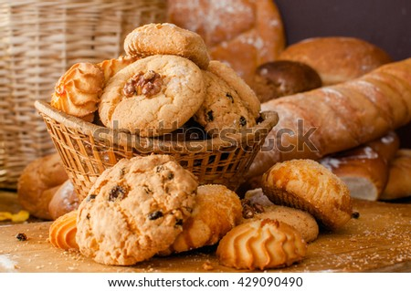 Cookies and sweet pastries in basket on wooden table