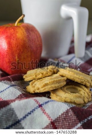 cookies, apple and cup of coffee on the cloth