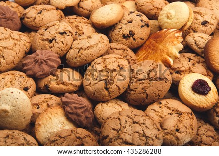 Cookies background. Sweet chocolate chips biscuits, shortbread and cookies with jam texture background. Oatmeal, chocolated drops and other sweets. Dessert, sweets for tea. Fattening sweets concept - stock photo