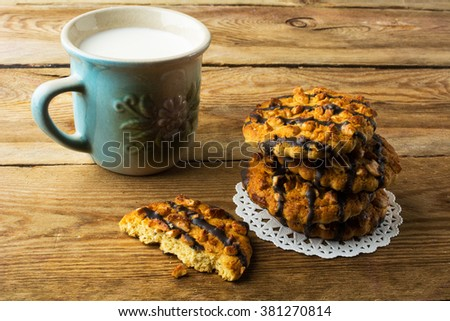 Cookies coating chocolate and milk on a rustic wooden table. Cookies. Pastry. Biscuits. Homemade cookies - stock photo
