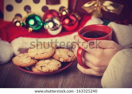 Cookies, cup of coffee and female hand with christmas gifts at background - stock photo