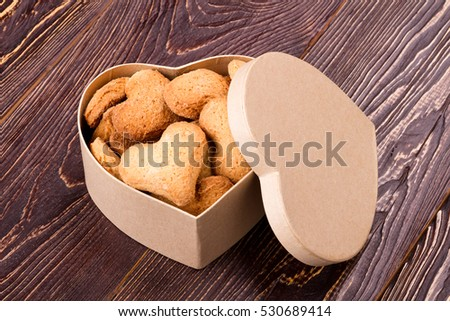 Cookies in box with lid. Biscuits in shape of heart. How to make pastry. Dessert baked at home.