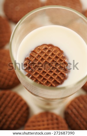 Cookies in glass of milk - stock photo