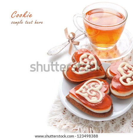 Cookies in the shape of a heart with cherry jelly and white chocolate and morning tea - stock photo