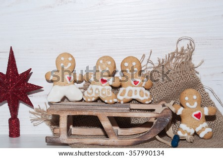 cookies in the shape of a little man near sled - stock photo