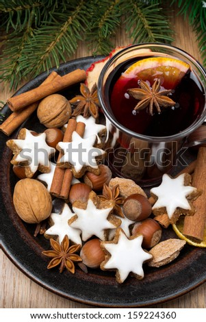 cookies in the shape of stars, spices and mulled wine on a plate, top view, vertical