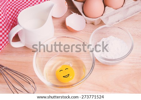 Cookies ingredients. Egg with smiling face in bowl, flour, milk, eggbeater,eggshells and red napkin - stock photo