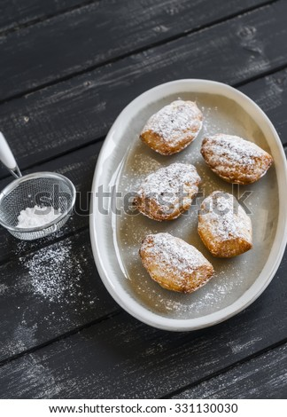 cookies madeleines with powdered sugar on oval plate on a light wooden surface - stock photo