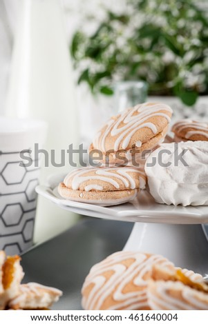 Cookies on white and gray plate with cups of coffee and bottles of milk on white shutters background with green and white flower