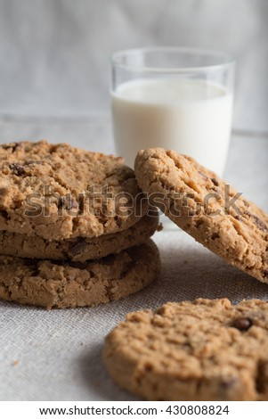 Cookies pile with chocolate chip on light textile background. Delicious morning snacks for breakfast, brunch and lunch. Appetizing, healthy, sweet, scrummy, and fast food. - stock photo