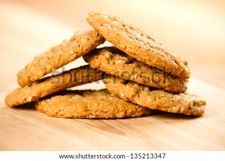 Cookies - This is a pile of homemade oatmeal cookies shot on a wooden cutting board. Shot with a shallow depth of field.