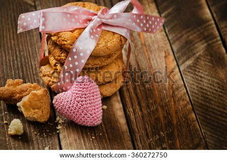 Cookies Valentine's Day cards with rose tape and knitting heart on wooden table.  - stock photo