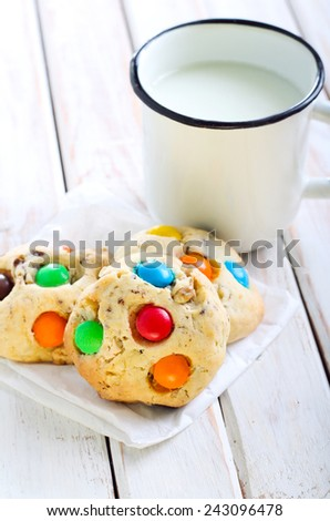 Cookies with colorful button shaped candies and milk - stock photo