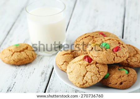 Cookies with colorful candy in plate on white wooden background - stock photo
