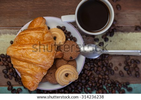 Cookies with croissant and coffee beans - stock photo