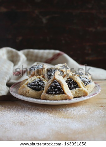Cookies with dried fruit filling and icing sugar for jewish holiday of purim - stock photo