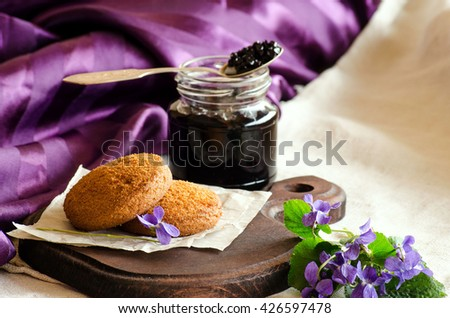 Cookies with elderberry jam and violet flowers on purple background - stock photo