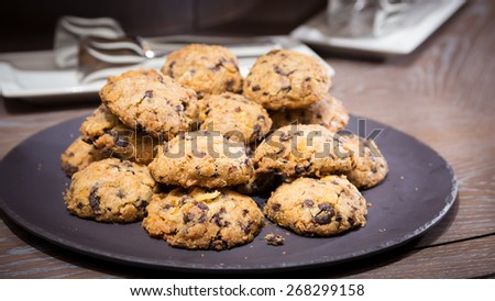 Cookies with raisins on wooden table. Shallow DOF and lightly toned. - stock photo