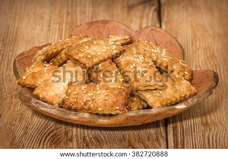 Cookies with sesame in the ceramic plate on the wooden background