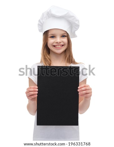 cooking, advertisement and food concept - smiling little chef, cook or baker with blank black paper - stock photo
