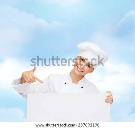 cooking, advertisement and people concept - smiling female chef, cook or baker pointing finger to white blank board over blue cloudy sky background - stock photo