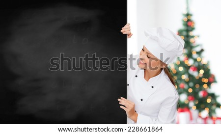 cooking, advertisement, holidays and people concept - smiling female chef, cook or baker with blank blackboard over living room and christmas tree background - stock photo