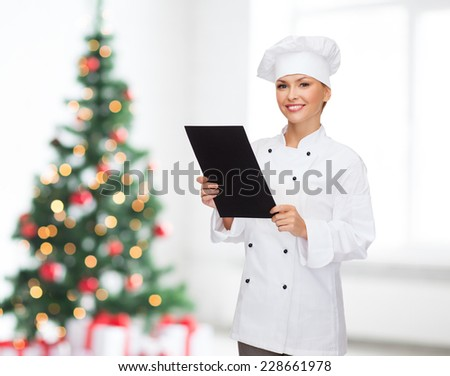 cooking, advertisement, holidays and people concept - smiling female chef, cook or baker with blank black menu paper over living room and christmas tree background - stock photo