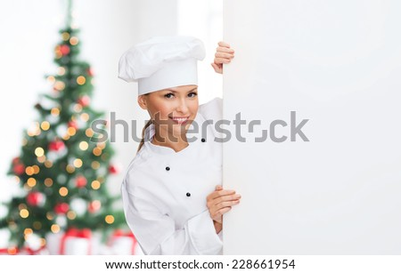 cooking, advertisement, holidays and people concept - smiling female chef, cook or baker with white blank board over living room and christmas tree background - stock photo
