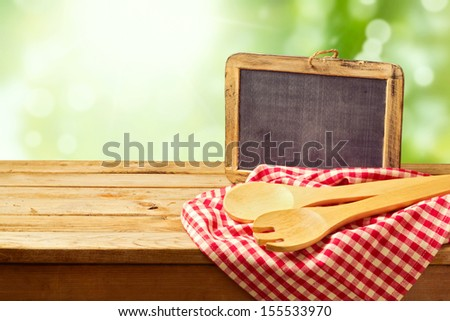 Cooking and backing background with wooden table and chalkboard over green bokeh - stock photo