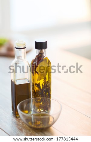 cooking and food concept - close up of two olive oil bottles and bowl of oil - stock photo
