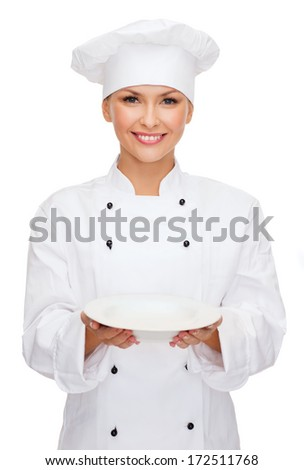 cooking and food concept - smiling female chef, cook or baker with empty plate - stock photo