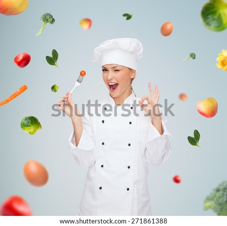 cooking and food concept - smiling female chef, cook or baker with fork and tomato showing ok sign over falling vegetables on gray background - stock photo