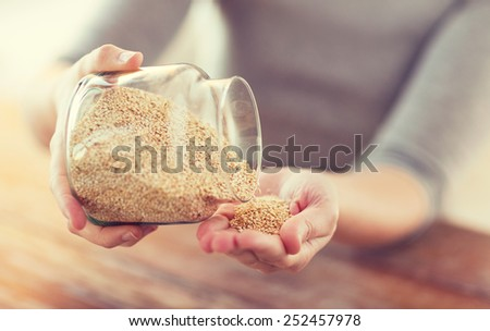 cooking and home concept - close up of female emptying jar with quinoa - stock photo