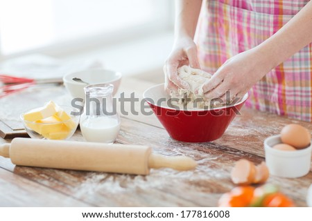 cooking and home concept - close up of female hands kneading dough at home - stock photo